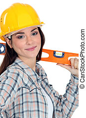 Female construction worker with a level.