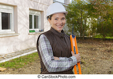 female construction worker with level at construction site