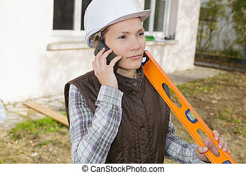 female construction worker with level outside construction site