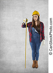 Female construction worker with meter, copy space