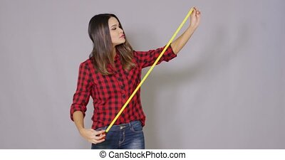 Female constructor worker with measure tape