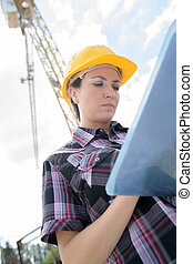 female contractor at a work site using an ipadtablet