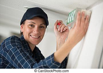 female contractor installing illuminated exit sign