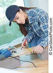 Female contractor measuring floorboard