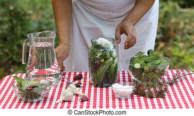 Female cook fills in salt and pours cucumbers for preservation. On the table is garlic, hot pepper, dill. Rustic background. The concept of natural eco-friendly food. Slow motion