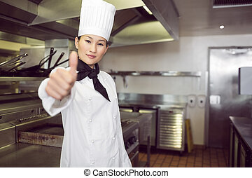 Female cook gesturing thumbs up in kitchen