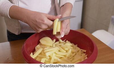 Female cook hands slicing potatoes home made fries in a bowl...