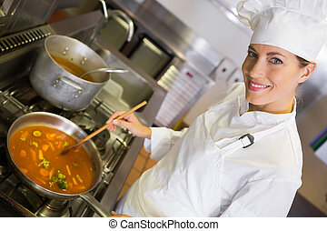 Female cook preparing food in kitchen - Side view portrait...