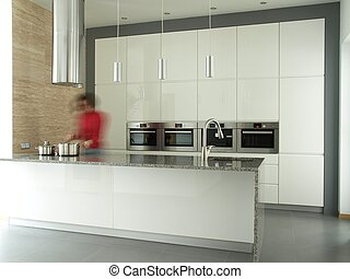Female cooking in modern minimalist kitchen in white color