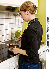 Female Cooking Supper in Kitchen - A female is cooking ...