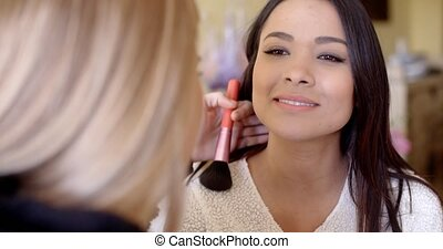 Female cosmetician working with client - Cosmetician holding...