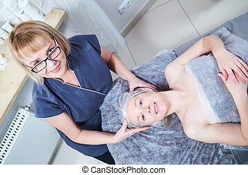 female cosmetologist beautician with client in beauty salon
