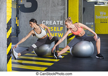 Female couple is doing fitness jointly in gym - Two sporty...