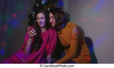 Female couple sitting near Christmas tree with glasses of wine watching videos