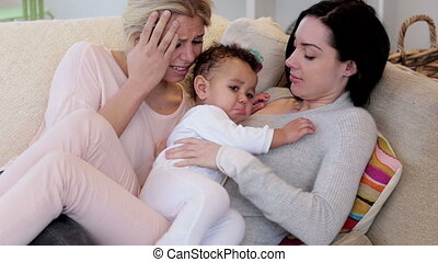 Female couple struggle with crying son - Female couple...