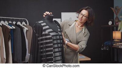 Professional female couturier designing new trendy dress on mannequin. Beautiful woman with brown hair having creative work at studio.