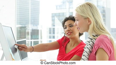 Female creative designer talking to colleagues