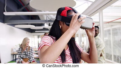 Female creative using VR goggles in a modern office - Front ...