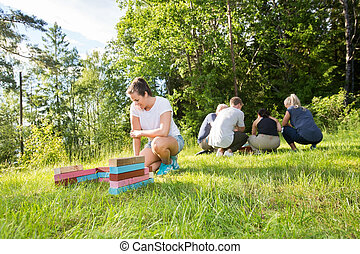 Female Crouching By Building Blocks While Friends Planning On Fi
