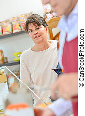 Female customer being served in a food shop