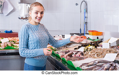 Female customer buying fish in shop
