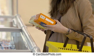 Female customer chooses the semi-finished products which are stored in the refrigerator