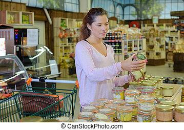 female customer choosing canned goods in food store