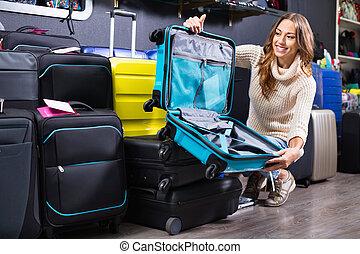 Female customer choosing travel suitcase