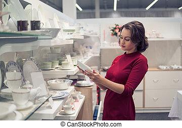 female customer choosing utensil dishes in the supermarket mall