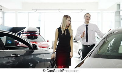 female customer comes to car, seller consultant tells about automobile