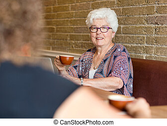 Female Customer Having Coffee In Cafe