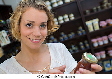 female customer holding a jar of jam