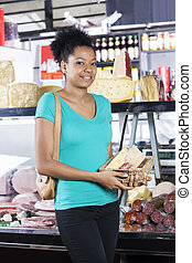 Female Customer Holding Cheese Basket In Grocery Store