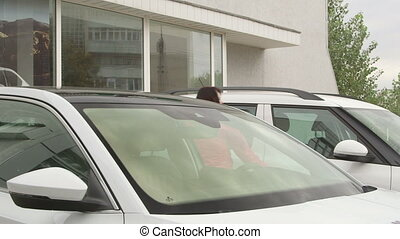 dealership showroom - Female customer looking inside new car...