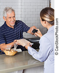 Female Customer Making Credit Card Payment At Counter