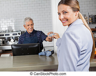 Female Customer Making Payment Through Credit Card In Store