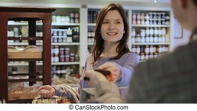 Female Customer Paying Sales Assistant For Shopping In...