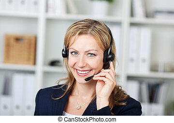 Closeup portrait of beautiful female customer service operator using headset in office