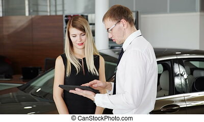 female customer shop consultant tells about automobile in car centre