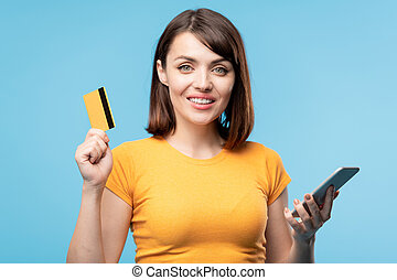 Female customer showing bank card while scrolling through promos in smartphone