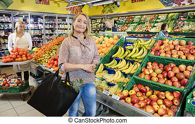 Female Customer Standing By Fresh Fruits In Grocery Shop