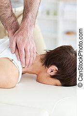 Female customer's neck massaged by masseur