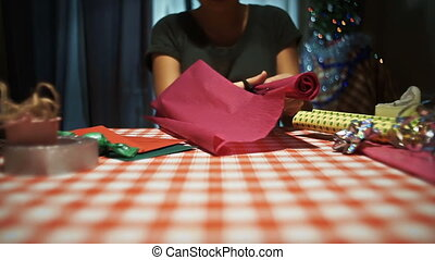 Female cutting pink wrapping paper for packing presents