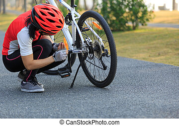 female cyclist fix the problem of mountain bike in park