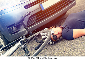 Female cyclist lying on the road