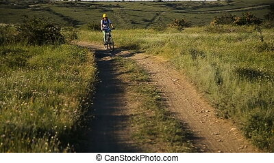 Female cyclist riding on a mountain road on a mountain bike.
