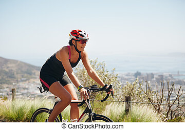 Female cyclist riding racing bicycle - Outdoor shot of a...