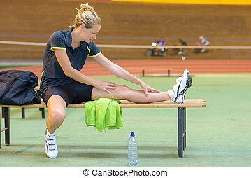 Female cyclist stretching leg