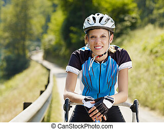 female cyclist - young woman on road bike. Copy space