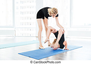 Female dance teacher doing stretching exercises with little gymnast girl
